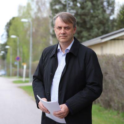 Vesa Ijäs, Lahti, on omakotiyhdistyksen puheenjohtaja. Kädessään paperinippu. Seisoo keväisessä maisemassa omakotitaloalueella.