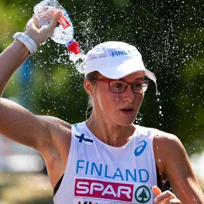 Tiia Kuikka kaataa pullosta vettä päähänsä.