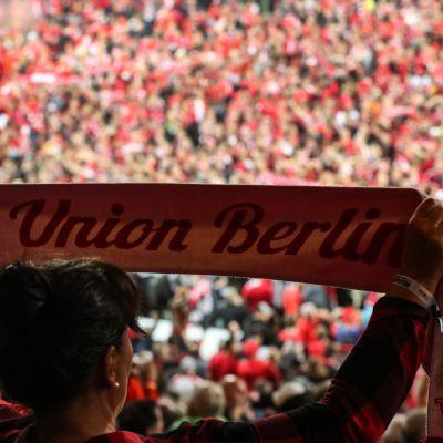 Union Berlinin kannattaja pitää seuran huivia, taustalla täysi stadion juhlii sarjanousua.