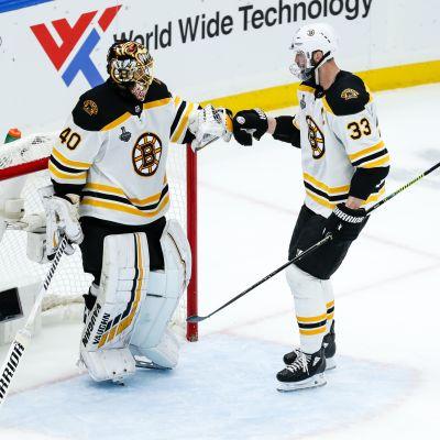 Boston Bruinsin pelaajat Tuukka Rask ja Zdeno Chara onnittelevat toisiaan voitetun ottelun jälkeen maalin edustalla.