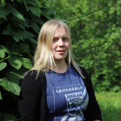 Susanna Valtonen hymyilee kesänvihreässä kuvassa.