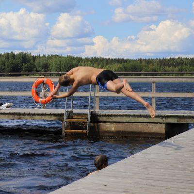 Poika hyppää veteen.