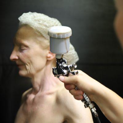Nainen suihkuttaa toista naista suihkurusketussumuttimella