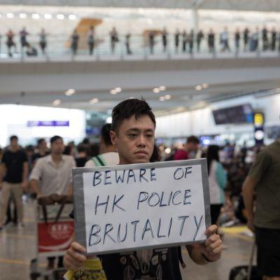 Mielenosoittaja kyltin kanssa Hongkongin lentokentällä