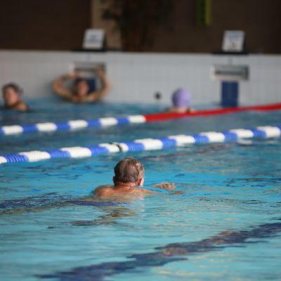Mies ui Karhulan uimahallissa.