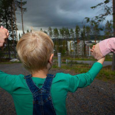 Lapsi kulkee vanhmpien kanssa käsi kädessä.