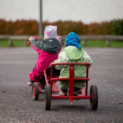 Lapset ajaa kolmipyörällä