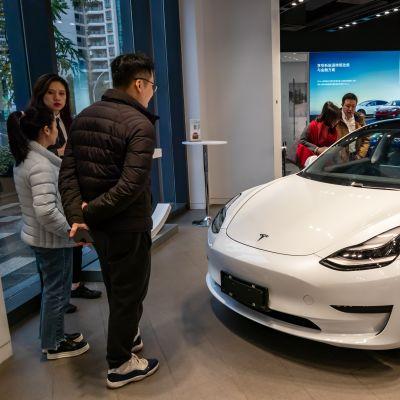 Asiakkaat tutkivat Tesla-autoa
