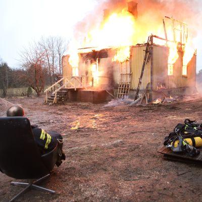 Palomies katsoo palavaa taloa.