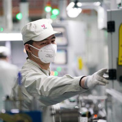 Kiinalainen teknikko työskentelee autotehtaassa hengityssuojain kasvoillaan.