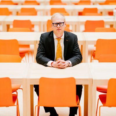 Pääanalyytikko Antti Saari istuu OP:n pääkonttorin ruokalassa, jonka tuolien väri on sama kuin konsernin logossa.