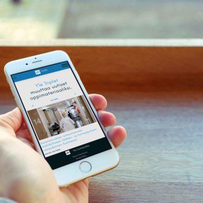 Kuvassa käsi, jossa on älypuhelin. Puhelimessa näkyy Triplet-sovellus.