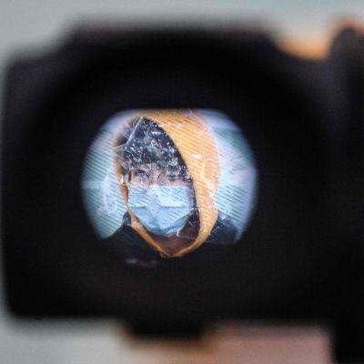 Videokamera tarkkailee matkustajaa Hongkongin lentokentällä.