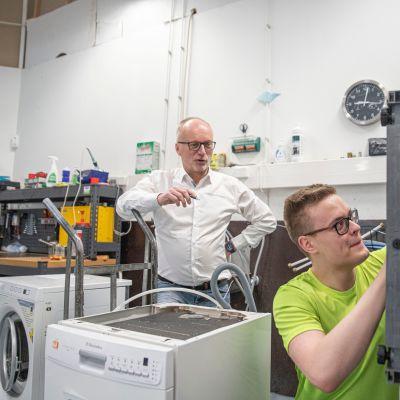 Toimitusjohtaja Esko Airaksinen ja huoltoasentaja Topi Tiainen tutkivat huoltoon saapuneita laitteita