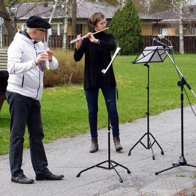 Pori Sinfoniettan huilistit Jukka-Pekka Lehto ja Lucia Hellerhoff soittamassa asukkaille Himmelin pihalla Porissa korona-aikaan.
