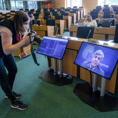 Valokuvaaja ottaa kuvaa televisioruudusta, jossa Euroryhmän puheenjohtaja Mario Centeno.