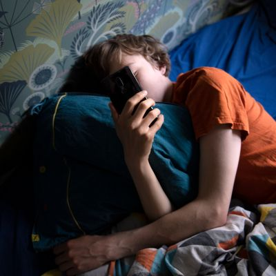 nuori selaa kännykkää vuoteessa