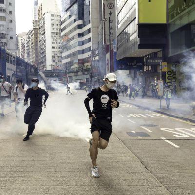 Mielenosoittajat pakenevat mellakkapoliisien kyynelkaasua.