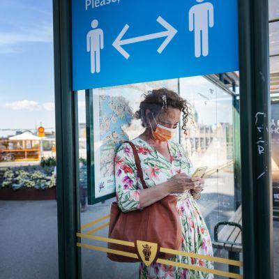 Nainen käyttää koronasuojusta Tukholmassa.