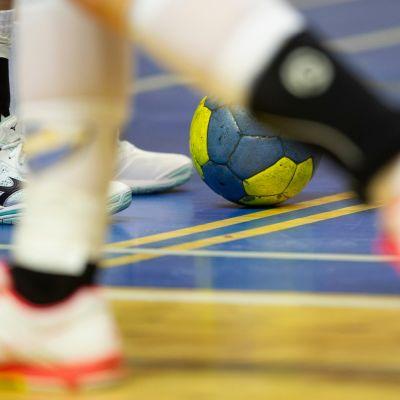 Kuvassa kahden käsipalloilijan jalat ja pallo.