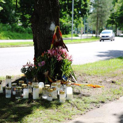 Kuvassa on kynttilöitä ja kukkia tien varressa puun juurella.