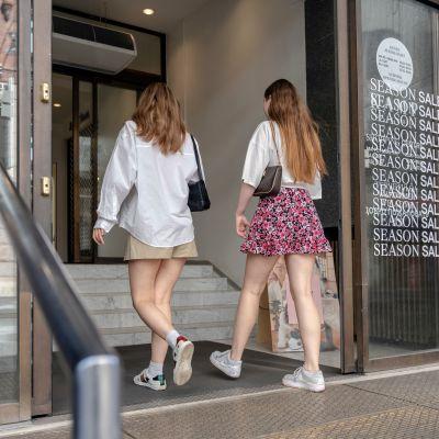 Kaksi nuorta henkilöä menee sisään myymälään, jossa on käynnissä alennusmyynti