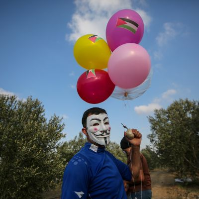 Gazassa polttopulloiskuja tekevä mies pitelee lähtövalmista ilmapallo-polttopulloa.