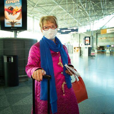 Liisa Hakala Helsinki-Vantaa lentoaseman lähtöaulussa. Liisalla on purppuran punainen takki, jossa pieniä kultaisia kuvioita ja sininen pitkä kaulaliina. Matkatavaroina on vedettävä pieni matkalaukku ja punainen käsilaukku. Kasvoilla on hengityssuojain.