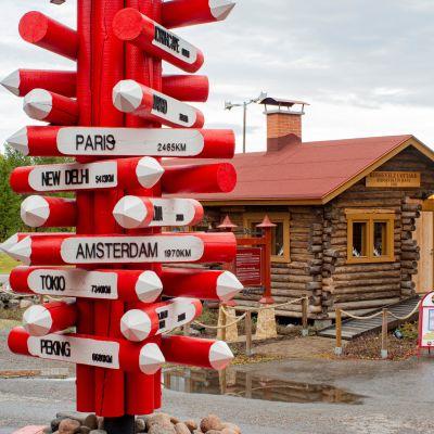 Napapiirillä sijaitseva kylttitolppa, josta voi lukea etäisyydet eri maailmankolkkiin.