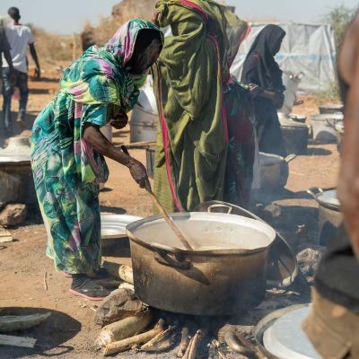 Nainen laittaa ruokaa pakolaisleirillä.