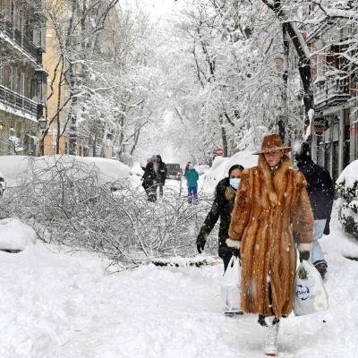 ihmisiä hyvin lumisella kadulla
