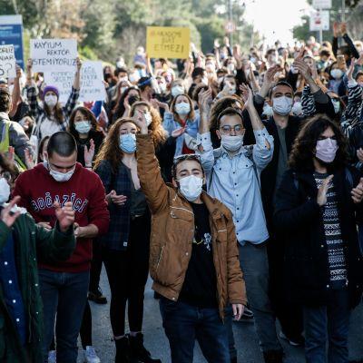 Mielenosoittajia koronamaskit kasvoillaan, käsissä kylttejä.