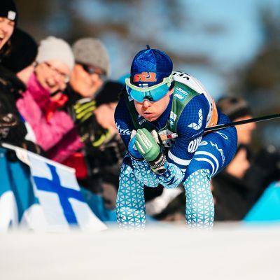 Krista Pärmäkoski laskee kisassa mäkeä ja puhaltelee posket pulleina.