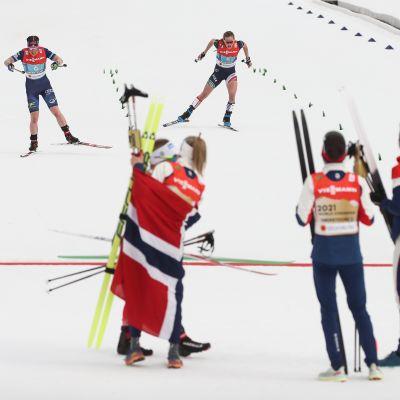 Norja juhlii naisten viestin voittoa maalissa. Taustalla Krista Pärmäkoski ja Jessie Diggins kirikamppailussa pronssista.