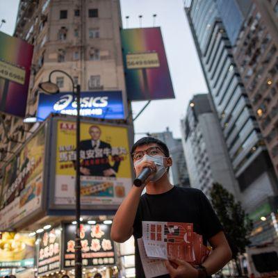 Hongkongin demokratia-aktivisti Joshua Wong Chi-fung  jakaa lentolehtisiä.