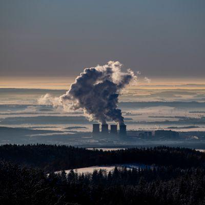 Hiilivoimala kuvattuna ylhäältä, piiput tupruttavat savua pilvien yli.