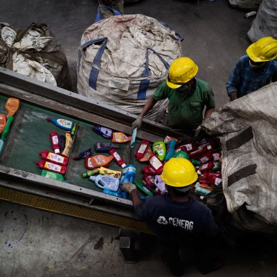 Kolme työntekijää kaataa suuresta säkistä käytettyjä muovipakkauksia liukuhihnalle.
