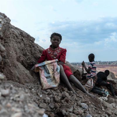 Punamekkoinen tyttö kerää kaivoksen rinteellä kobolttiä säkkiin. Taustalla myös muita lapsia.
