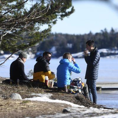Fyra män sitter och äter matsäck på en strand. Det är vår, mend lite snö på marken. Männen är varmt klädda.