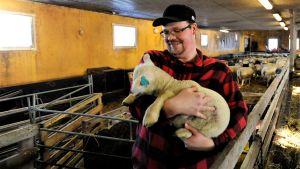 Fårfarmare Fredric Bränn inne i fårgården med ett lamm i famnen