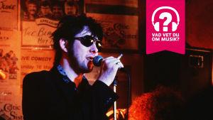 Shane MacGowan har solglasögon, en cigarrett i handen och sjunger i en mikrofon.