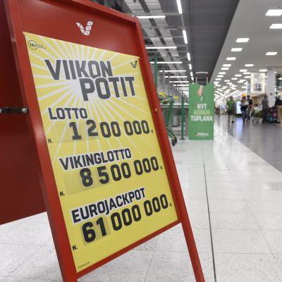 En reklamskylt med lottovinster står i en matbutik.