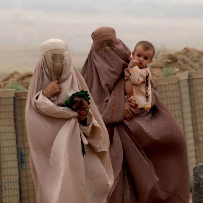 Två kvinnor i burqa bär sina barn i Khakrez, Afghanistan.