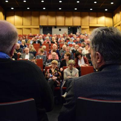 Två personer fotade bakifrån med fullsatt publik.