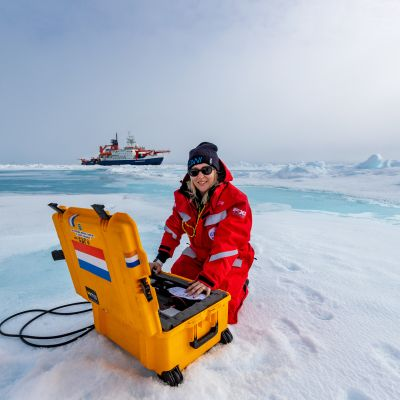 Aurinkolasipäinen tutkija punaisessa suojahaalariss  keltaisen muovilaatikon ääressä. Takana jäävalleja ja tutkimusalus.