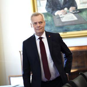 Antti rinne står i ett rum i kostym, i bakgrunden syns en tavla med guldram