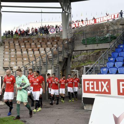 HIFK-spelarna går in på plan med supportarna i bakgrunden.