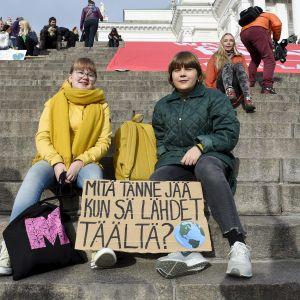 Demonstranter väntar på att klimatmarschen ska börja på Domkyrkans trappa i Helsingfors.