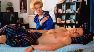 En kvinna i festklänning sitter lutad över en naken man som sover i en säng.
