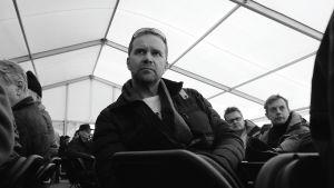 Mies istuu jonkinlaisessa tilaisuudessa, takana muita miehiä istumassa